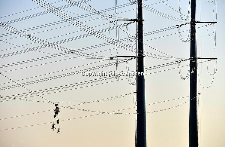 Nederland, Silvolde, 14-2-2017Tussen Doetinchem en de Duitse grens wordt dooronderaannemer SPIE iov netwerkbehheerder Tennet een nieuwe hoogspanningsleiding aangelegd. Het gaat om een 380 kilovolt-leiding, de zwaarste spanning die we in Nederland hebben. Een medewerker van de aannemer bevstigd losse componenten aan de kabel. Hij fietst zichzelf over de kabel. De stroomdraden moeten de uitwisseling van met name groene stroom tussen Nederland en Duitsland bevorderen.Het gaat om dubbele masten van een nieuw ontwerp: iedere mast bestaat uit twee pylonen van zo'n 60 meter hoog.De nieuwe leiding loopt van hoogspanningsstation Langerak bij Doetinchem naar het Duitse Wesel, een afstand van 57 kilometer. Daarvan ligt 22,5 kilometer op Nederlands grondgebied. Foto: Flip Franssen