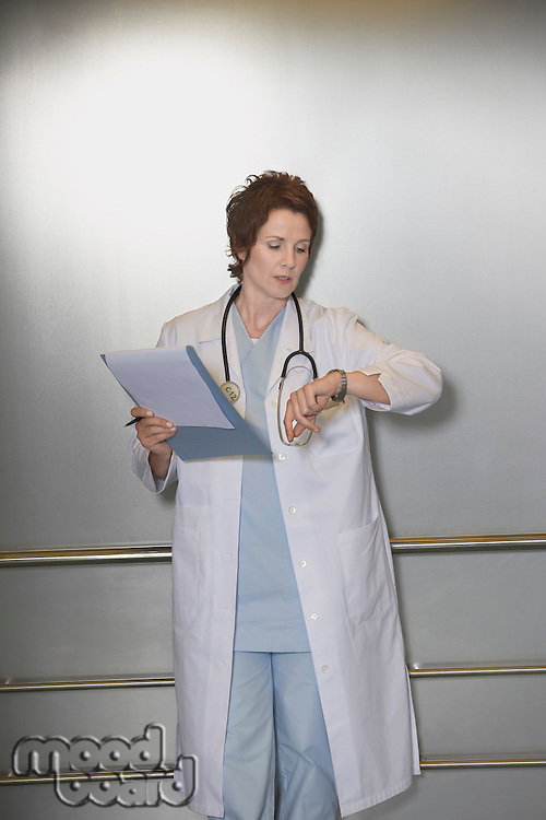 Physician Checking Wristwatch in elevator
