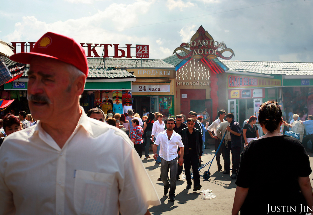 Shoppers browse goods at the Cherkizovo market in eastern Moscow soon after .an explosion killed 10 people, including two children, and injuring more than 40..Prosecutors said the attack was likely linked to organized crime, though terrorism could not be ruled out..The explosion crashed the roof of around 100 sq meters and triggering the fire.