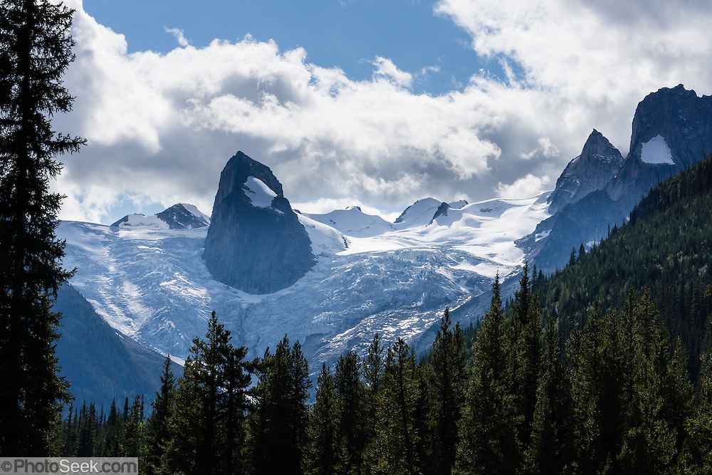 "The Hound's Tooth (2819 meters) rises above Bugaboo Glacier in Bugaboo Provincial Park, in the Purcell Range of the Columbia Mountains, British Columbia, Canada. Most tourists are attracted by nearby Canadian Rockies parks along fast paved highways and skip gravel logging roads, thereby leaving the spectacular ""Bugaboos"" as a quiet retreat for hikers, climbers, and luxury CMH helicopter guests. Directions: From Brisco (about 44 kms north of Invermere on Hwy 95), follow signs to Bugaboo Provincial Park and CMH Lodge on a gravel logging road. After 47 kms, turn right on a rougher road to reach Cobalt Lake trail head and Kain Hut trail head, or continue straight along Bugaboo Forest Service Road. Before you reach the gate of luxury CMH Bugaboo Lodge, a left turn crosses Bugaboo Creek bridge: then a left reaches Bugaboo Septet Recreation Site (4 primitive campsites in a free, user-maintained campground reachable by 2WD vehicles) or straight up takes 4WD vehicles and hikers to Chalice Creek trailhead."