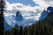 """The Hound's Tooth (2819 meters) rises above Bugaboo Glacier in Bugaboo Provincial Park, in the Purcell Range of the Columbia Mountains, British Columbia, Canada. Most tourists are attracted by nearby Canadian Rockies parks along fast paved highways and skip gravel logging roads, thereby leaving the spectacular """"Bugaboos"""" as a quiet retreat for hikers, climbers, and luxury CMH helicopter guests. Directions: From Brisco (about 44 kms north of Invermere on Hwy 95), follow signs to Bugaboo Provincial Park and CMH Lodge on a gravel logging road. After 47 kms, turn right on a rougher road to reach Cobalt Lake trail head and Kain Hut trail head, or continue straight along Bugaboo Forest Service Road. Before you reach the gate of luxury CMH Bugaboo Lodge, a left turn crosses Bugaboo Creek bridge: then a left reaches Bugaboo Septet Recreation Site (4 primitive campsites in a free, user-maintained campground reachable by 2WD vehicles) or straight up takes 4WD vehicles and hikers to Chalice Creek trailhead."""