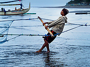 29 JULY 2017 - AIRKUNING, BALI, INDONESIA: A fisherman in Airkuning, a Muslim fishing village on the southwest corner of Bali, haul in a fishing net that had been laid by outrigger canoes from the village. Villagers said their regular catch of fish has been diminishing for several years, and that are some mornings that they come back to shore with having caught any fish.    PHOTO BY JACK KURTZ