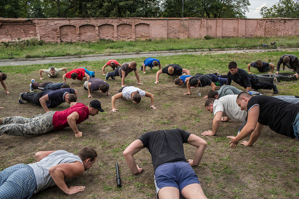 LVIV, UKRAINE - OCTOBER 5, 2015: Recruits do push-ups during tactical training for new patrol police officers in Lviv, Ukraine. In an effort to reform the notoriously corrupt Ukrainian police force, an entirely new force has been established in several cities, including Kiev and Lviv, with a primary focus on patrolling the streets. CREDIT: Brendan Hoffman for The New York Times