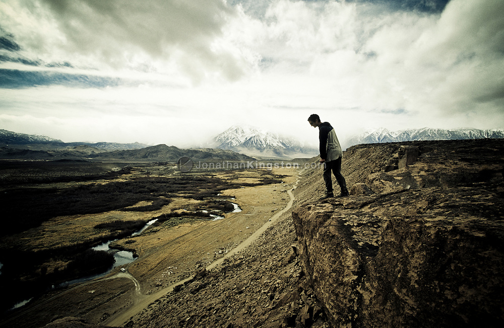 One man looks down the cliff face of a lava butte known as the Volcanic Tablelands, overlooking the Owens river valley with a view of snow capped Mt. Tom in the background, Bishop, California. (releasecode: jk_mr1016) (Model Released)