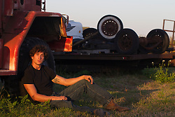Good looking twenty something year old man in a black tee shirt and jeans outdoors in a car junk yard at sunset