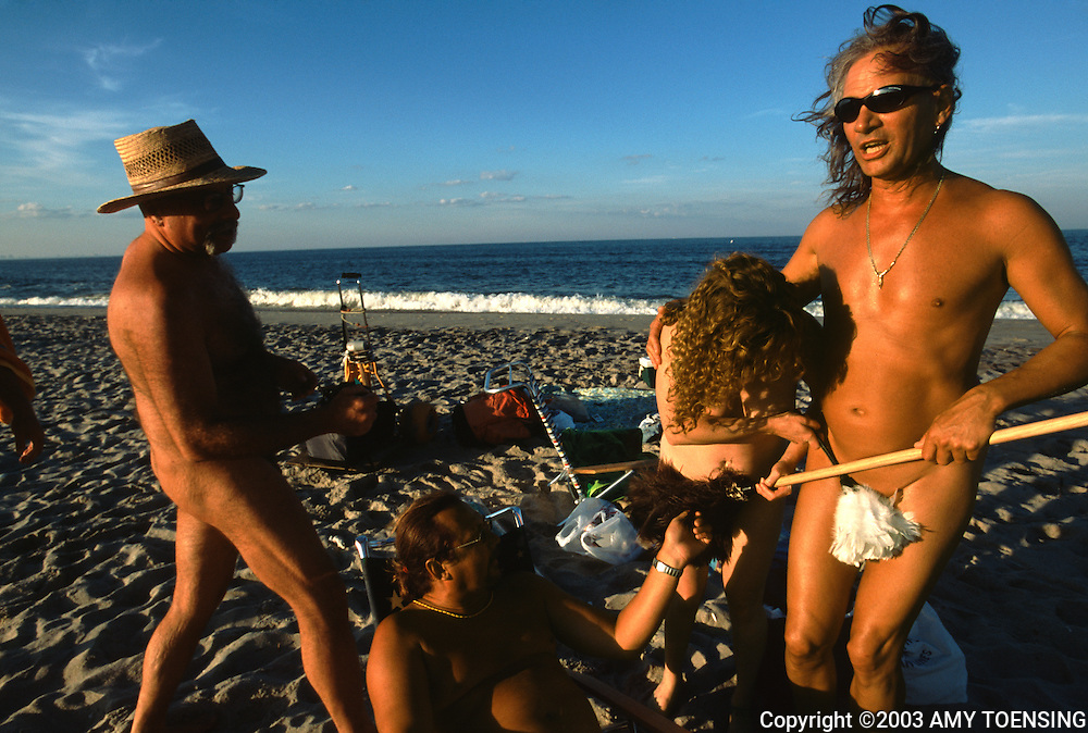 SANDY HOOK, NJ - JULY 12: Friends hide each others' private parts with feather dusters on the clothing optional area of Gunnison Beach, July 12, 2003, Sandy Hook, New Jersey. Gunnison is part of the Gateway National Recreational Area and has been a destination for nudists since the 1970s. Many of its visitors have been enjoying the sun and socializing there since its beginning. The Jersey Shore, a 127 mile stretch of coastline known for its variety of beaches, boardwalks, small towns, natural beauty and summer crowds, has been a popular summer destination for over a century. (Photo By Amy Toensing)