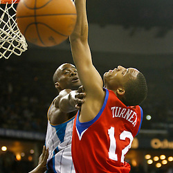 January 3, 2011; New Orleans, LA, USA; Philadelphia 76ers shooting guard Evan Turner (12) loses control of the ball as New Orleans Hornets center Emeka Okafor (50) defends during the second quarter at the New Orleans Arena.   Mandatory Credit: Derick E. Hingle