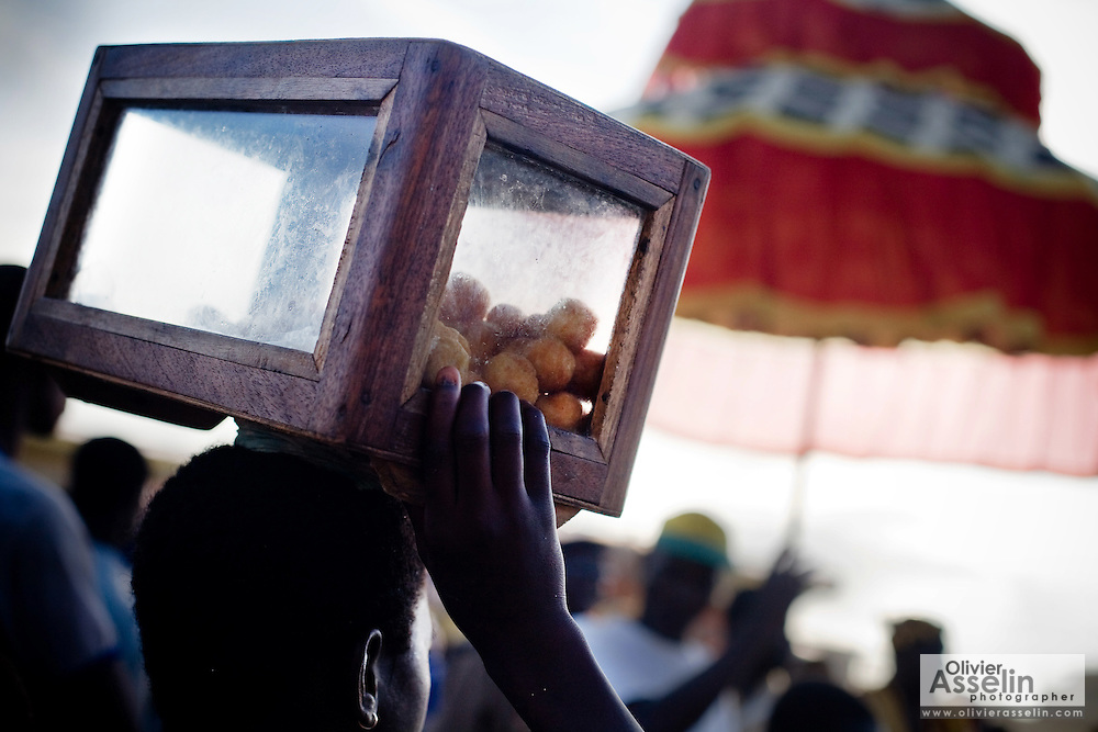 A girl carries a box filled with fried balls of dough she tries to sell as snacks during the annual Oguaa Fetu Afahye Festival in Cape Coast, Ghana on Saturday September 6, 2008.
