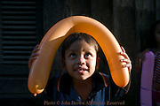 A young boy is playing with a balloon near Boeung Kok Lake in Phnom Penh, Cambodia.