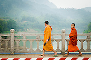 Laos, Nong Khiaw. Two novice monks walking on the bridge connecting two parts of the village.