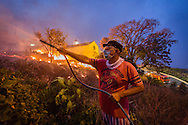 A man uses a garden hose to extinguish a fire in the city of Funchal, Madeira island, Portugal, 10 August 2016. Wild fires on the Madeira island have destroyed several buildings in the capital and reportedly killing at least three people. EPA/GREGORIO CUNHA