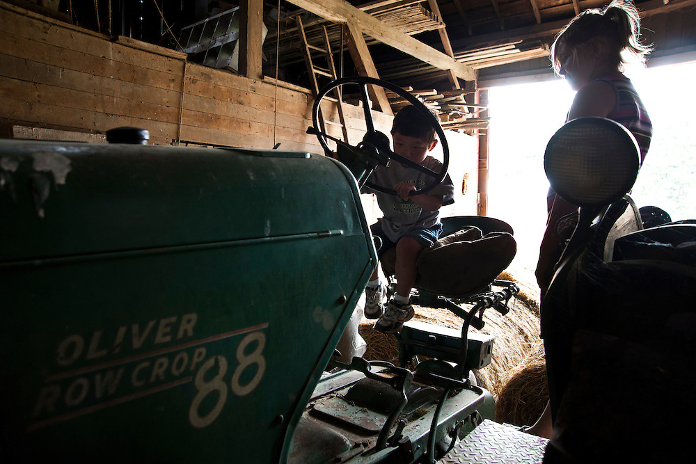 Holden Miller, almost 3, enjoys playing with his cousin, Rachel, and exploring a vintage tractor parked in a barn at Jim and Michele Stute's farm in East Troy, Wis., on May 31, 2010.