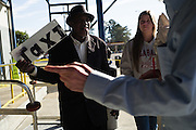 "MONTGOMERY, AL – JANUARY 25, 2016: Michael Harris (left) courts travelers from Nashville as they arrive at the Greyhound bus station. In 2011, the downtown Montgomery Greyhound bus station was converted into a museum to honor the freedom riders, who endured a violent attack there in 1961. The replacement bus station, located four miles from downtown, is a prime business opportunity for independent cabbies like Michael Harris, who make a living serving passengers unwilling to rely on city buses. Many characterize the public bus system in Montgomery as unsafe and unreliable, so wary passengers cough up $2 per mile for trips in Mr. Harris' 2005 Lincoln Navigator, traveling across town for fast food, or sometimes as far as New York City. ""This is my life,"" Harris said. ""I love driving, and I help people out. It's just in my heart."""