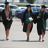 Shanda Green, from left, Tiana Valencia and Savanna Moses make their way across the parking lot for their graduation at the BancorpSouth Arena Saturday.