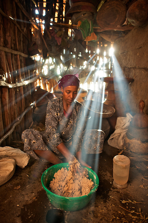 Tayitis Mohammed mixes injera out of teff flower and water in her house in Fontanina near Kombulcha in the Wollo region of the Ethiopian highlands. Injera is the staple bread of Ethiopia, which makes teff a valuable grain. Smoke from the kitchen fire made the rays of the setting sun show up brightly in the dark cookng area to the side of the main room of the stick and clay built house. The walls of the house are caulked with teff straw as well.<br /> <br /> The injera batter, a bit runny like pancake batter, is then transfer to the bucket last used to &quot;ferment&quot; the injera for a couple of days, picking up the residual yeasts in the bucket and providing leavening to the bread.