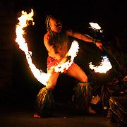 A native Hawaiian juggles fire torches at a Luau in Kaanapoli, Maui.