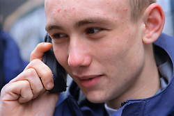 Portrait of teenage young offender using mobile phone,