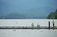 Fishermen line the dock on Hayden Lake as a swimmer does laps Tuesday at Honeysuckle Beach.