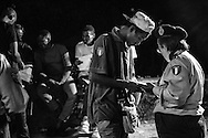 A Red Cross volounteer assisting a young migrant in the station park at night