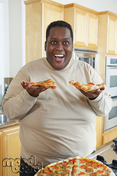 Man holding slices of pizza and laughing