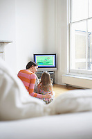 Mother and daughter (5-6) watching cartoons in television back view