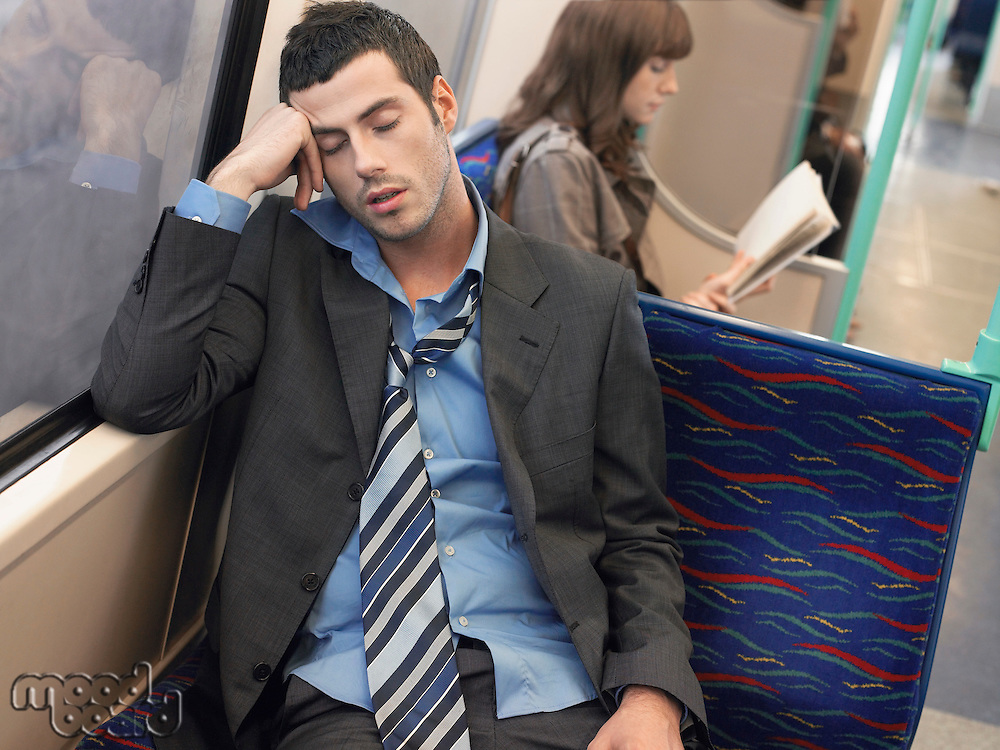 Businessman with loosened tie sleeping on Commuter Train