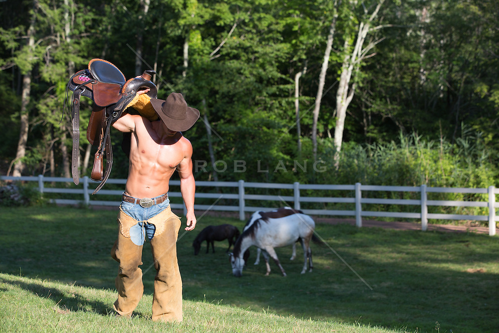 shirtless hunky cowboy carrying a saddle on a ranch