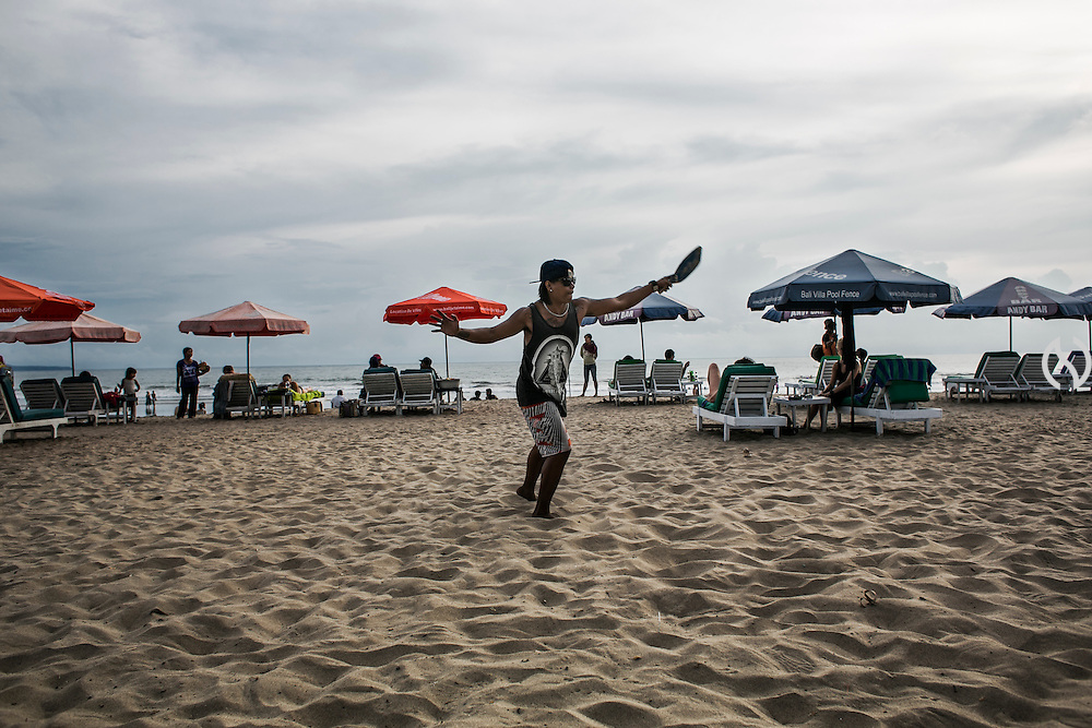 BALI, INDONESIA; APRIL 23, 2015: A drink vendor plays beach tennis at Double Six beach, Bali, Indonesia on Thursday, April 23, 2015.
