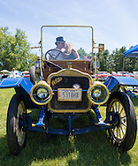 Old Westbury, New York. United States. 7th June 2015. SAM GRECO and LAURA GRECO, of Garden City Park, are kissing each other as they sit in their blue 1910 White at the 50th Annual Spring Meet Car Show sponsored by Greater New York Region Antique Automobile Club of America. Over 1,000 antique, classic, and custom cars participated at the popular Long Island vintage car show held at historic Old Westbury Gardens.