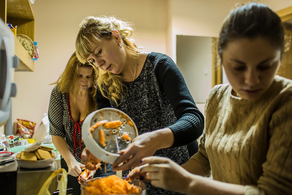 DNIPROPETROVSK, UKRAINE - NOVEMBER 16, 2014:  Alyona Fedorenko, 36, an economist, left, Tatyana Sirko, 42, a gynecologist, center, and Zhanna Kuzmytska, 23, a psychologist, right, package the dried ingredients for traditional borscht soup in the kitchen at the Dnipropetrovsk Volunteer Logistics Center, a charity organization that produces supplies for pro-Ukrainian fighters battling rebels in the country's East, in Dnipropetrovsk, Ukraine. CREDIT: Brendan Hoffman for The New York Times