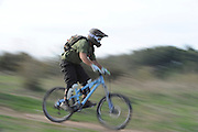 Mountain bike cyclist zooms past camera on a nature trail motion blur affect