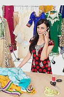 Pretty Indian female dressmaker answering phone call while standing at table
