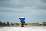 A woman carries a bucket full of salt from the shore at the Lac Rose near Dakar, Senegal, on Tuesday, July 26, 2016. *** Second Sentence *** Photographer: Xaume Olleros/Bloomberg