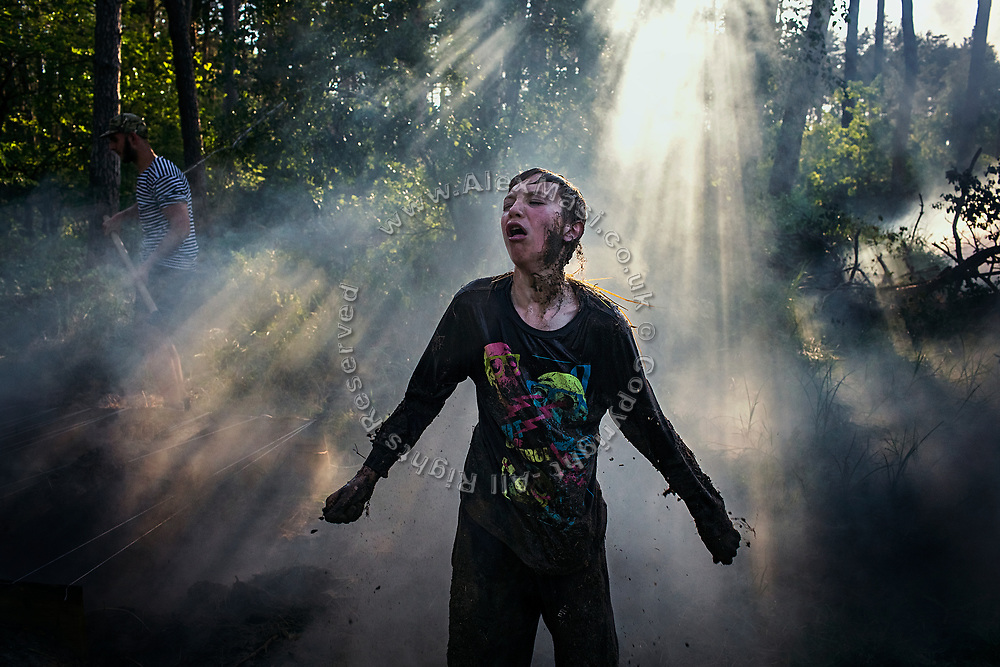 A young man participating to the ultra-nationalistic Azovets children's camp is coughing hard during a physical and tactical training involving an obstacle course in a forest near the village of Buzova, 30 km west of Kiev, the capital of Ukraine.