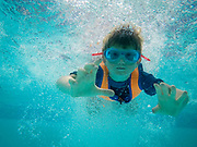 A 5 year old boy swimming underwater in a pool wearing goggles and a life vest looking happy and holding his breadth. This image is Model Released. (photo by Andrew Aitchison / In pictures via Getty Images)