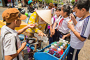 "12 APRIL 2012 - HO CHI MINH CITY, VIETNAM:  Schoolchildren buy shaved ice from a vendor in Cholon, the Chinese-influenced section of Ho Chi Minh City (former Saigon). It is the largest ""Chinatown"" in Vietnam. Cholon consists of the western half of District 5 as well as several adjoining neighborhoods in District 6. The Vietnamese name Cholon literally means ""big"" (lon) ""market"" (cho). Incorporated in 1879 as a city 11 km from central Saigon. By the 1930s, it had expanded to the city limit of Saigon. On April 27, 1931, French colonial authorities merged the two cities to form Saigon-Cholon. In 1956, ""Cholon"" was dropped from the name and the city became known as Saigon. During the Vietnam War (called the American War by the Vietnamese), soldiers and deserters from the United States Army maintained a thriving black market in Cholon, trading in various American and especially U.S Army-issue items.         PHOTO BY JACK KURTZ"