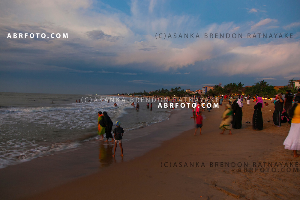 A large group of Beachgoers playing along the shoreline of Negombo beach as teh sun sets. Negombo is a major city in Sri Lanka, located on the west coast of the island and at the mouth of the Negombo Lagoon