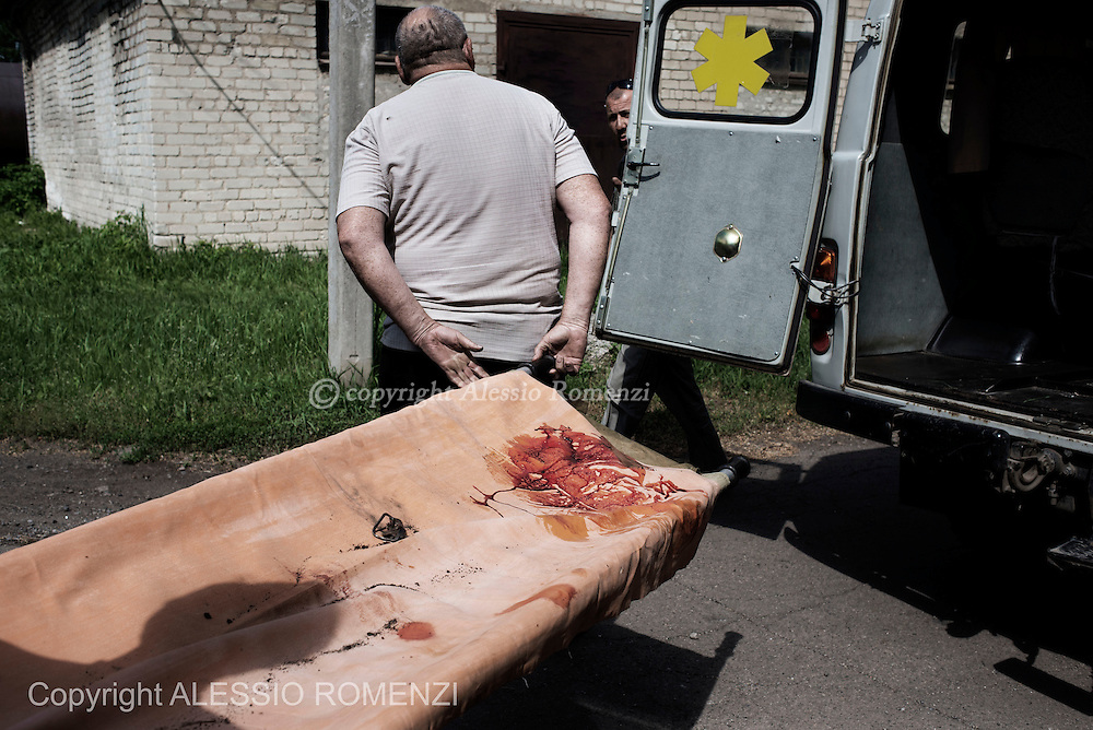 Ukraine, Volnovakha. The still bloodstained stretcher used to carried the body of an Ukrainian soldier is carried outside the morgue of Volnovakha's hospital on May 22. At dawn an Ukrainian army check point near the village of Blahodatne has been attacked by unknown armed men and have been reported at least 13 killed and 30 injured. ALESSIO ROMENZI