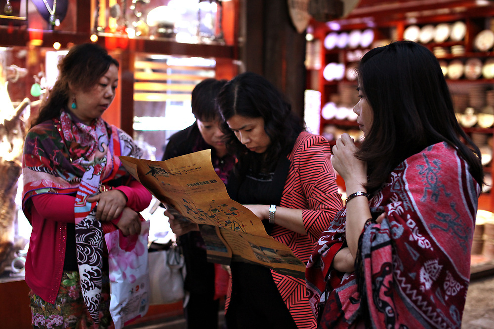 Chinese tourists consult a map in old-town Lijiang, Yunnan, China; September, 2013.
