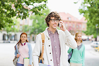 Smiling young male student using cell phone with friends in background on street