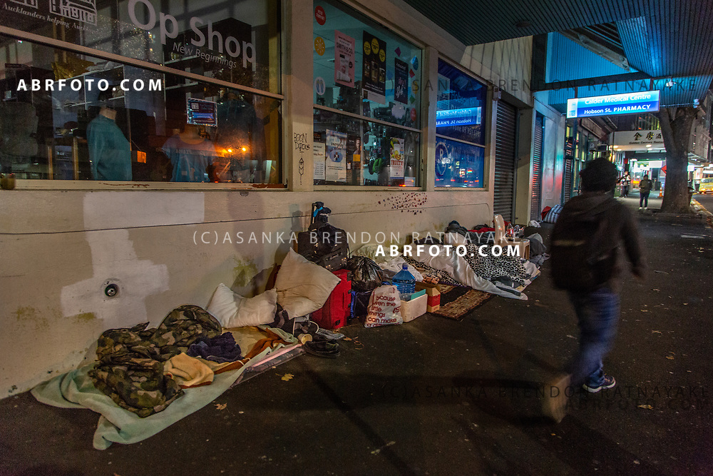 A person walks past a collection of blankets, pillows and other essentials belonging to the homeless kept outside a pharmacy next to the Auckland city mission on the 6th of June 2018. Asanka Brendon Ratnayake for The New York Times.