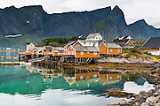 Yellow rorbuer (fishing shanties rented for lodging) rise on stilts over Reinefjord beneath impressive mountain peaks in the Lofoten archipelago, Nordland county, Norway. Sharply glaciated peaks rise on Moskenesøya (the Moskenes Island) above the Norwegian Sea.
