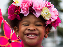 London, August 30th 2015. A little girl smiles for the camera as revellers enjoy Family Day at the Notting Hill Carnival.