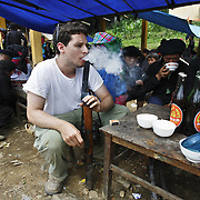 Benjamin Reich, of the UpperWest Side of Manhattan, NYC, smokes tobacco from a bamboo pipe at the Sa Phin market in Ha Giang, Vietnam's northernmost province, 23 June, 2007. Reich is working as a businessman in Hanoi, where he has lived for 10 years. As cities like Hanoi and Ho Chi Minh roar with Vietnam's economic boom, Ha Giang remains a quiet, serene and beautiful mountain backwater along the Chinese border.