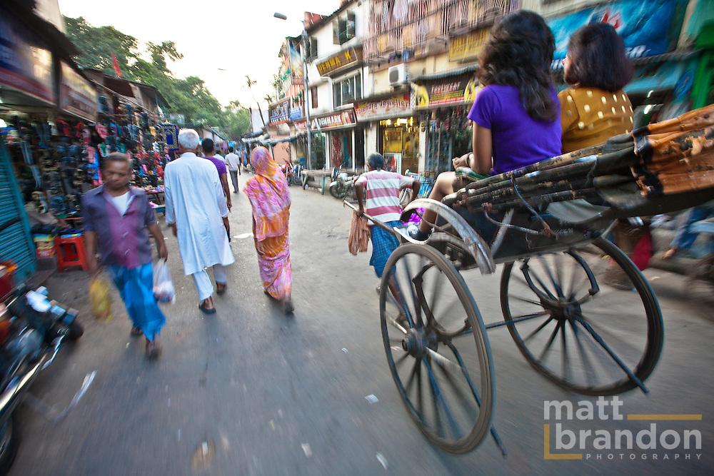 A rickshaw driver navigates the narrow streets of the market in Kolkata.