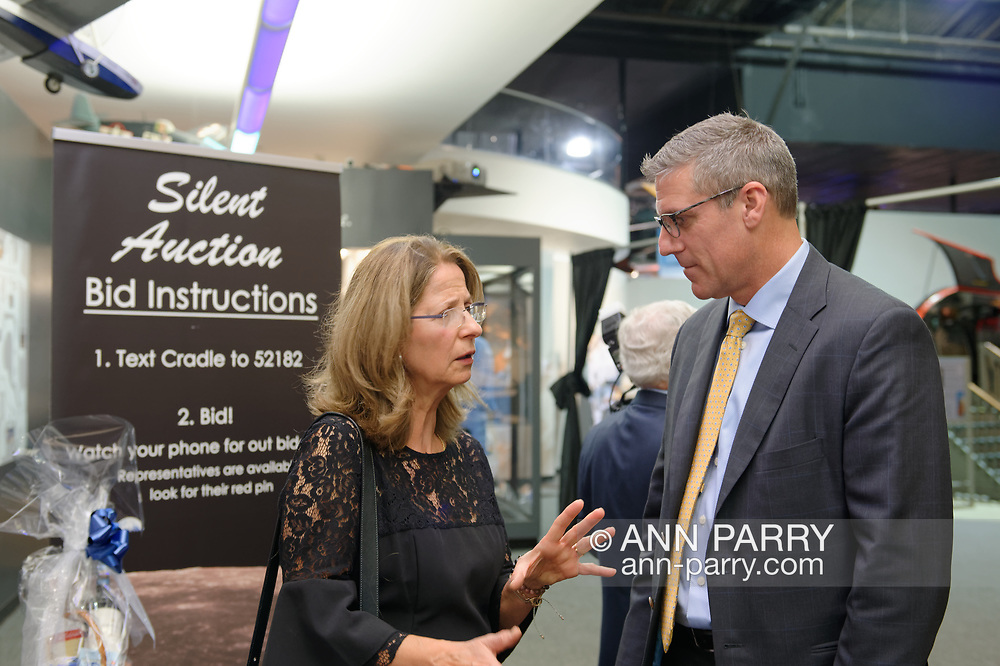 Garden City, New York, U.S. November 14, 2019. L-R, ROSE MOLINS, a nurse whose husband is Vice President & General Counsel the Americas at Lufthansa German Airlines, and KEVIN CORRIGAN, Sr. Vice President AvAir Pros, talk with each other near the Silent Auction sign in the fundraiser display area during the during the 17th Annual Cradle of Aviation Museum Air and Space Gala.