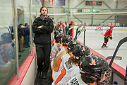 The West coach,<br /> Nathan Shasby, watches the game and clock during the second period of the 2015 State Hockey Championships at the Curtis D. Menard Memorial Sports Center Saturday night. WHS won 4-3.