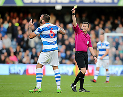 QPR's Joel Lynch receives a yellow card off referee Tony Harrington for a challenge on Wolves Bright Enobakhare during the Sky Bet Championship match at Loftus Road, London.