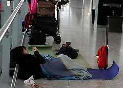 © Licensed to London News Pictures. 06/02/2012, Heathrow, UK. A Passenger waits for their flight with a blanket and a camping mat in Terminal 5. Snow and heavy fog continue to disrupt flights at Heathrow Airport today 6th February 2012. Heavy snow fell over many parts of the South East of the UK over Saturday night.  Photo credit : Stephen Simpson/LNP
