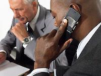 Businessman using mobile phone in meeting